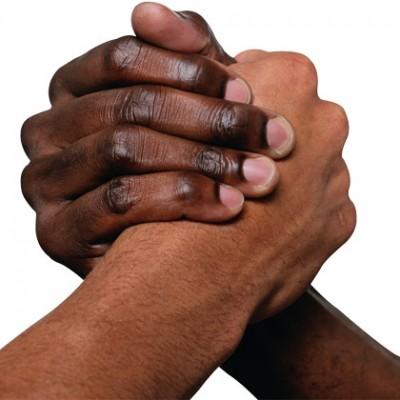 due mani si stringono, una bianca e una nera